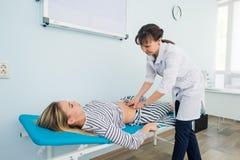 Doktorski sprawdzać żołądek jeden jej pacjenci Zdjęcia Royalty Free