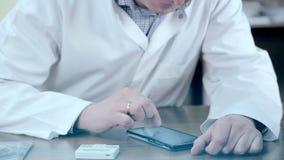 Doktorski używać telefon komórkowego i pastylkę Męska lekarka używa urządzenia elektroniczne zbiory wideo