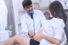 Doktorski używa stetoskopu biały egzamininuje kobieta w ciąży Obraz Stock