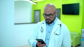 Doktorski używa telefon komórkowy tekst Męska lekarka używa telefon komórkowego Doktorski używać smartphone zbiory