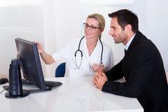 Doktorski wyjaśniający coś męski pacjent Fotografia Royalty Free