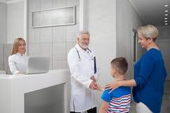Doktorskie chwianie ręki z chłopiec na konsultacji fotografia stock
