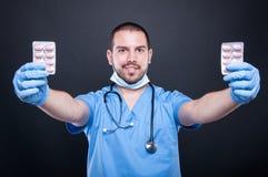 Doktorskie jest ubranym pętaczki pokazuje dwa pastylek bąbel Zdjęcia Stock