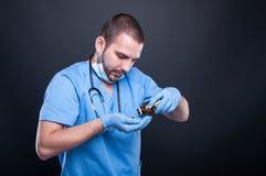 Doktorskie jest ubranym pętaczki rozlewa wybory od butelki Fotografia Stock