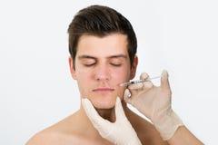 Doktorskie ręki Wstrzykuje Botox zastrzyka W mężczyzna twarzy obraz royalty free