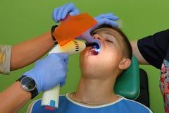 Doktorskie ` s ręki w błękitnych rękawiczkach dołącza wsporniki na nastolatka ` s zębach Obraz Royalty Free