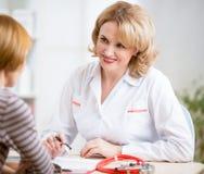 Doktorskiej kobiety życzliwy opowiadać pacjent w ona Zdjęcia Stock