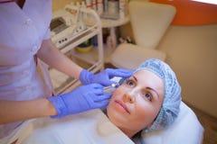 Doktorskosmetologen ökar kantpatienten en injektioninjektionsspruta Royaltyfri Foto