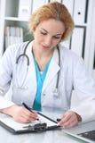 Doktorskvinna på arbete Form för rekord för medicinsk historia för läkarepåfyllning på skrivbordet Medicin sjukvårdbegrepp royaltyfria bilder