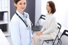 Doktorskvinna på arbete Stående av gladlynt le för kvinnlig läkare, medan stå det near mottagandeskrivbordet på kliniken eller arkivbilder