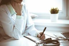 Doktorskvinna som arbetar med formen f?r l?karbehandlinghistorierekord, medan sitta p? skrivbordet n?ra f?nster i sjukhus Medicin royaltyfri foto