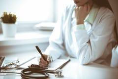Doktorskvinna som arbetar med formen f?r l?karbehandlinghistorierekord, medan sitta p? skrivbordet n?ra f?nster i sjukhus Medicin royaltyfria bilder