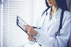 Doktorskvinna som arbetar med formen f?r l?karbehandlinghistorierekord, medan st? n?ra f?nster i klinik care h?lsomedicinen royaltyfri fotografi