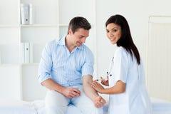 doktorskvinnlig som ger tålmodign som ler till vaccinet arkivfoton