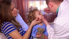 Doktorsman som ger skeden av medicin till barnsammanträde i säng med hans moder stock video