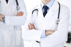 Doktorsmananseende som ?r rakt med kollegan p? bakgrund, n?rbild Grupp av doktorer Perfekt medicinsk service i klinik arkivfoto