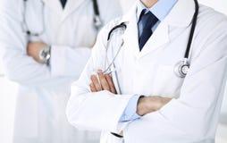 Doktorsmananseende som ?r rakt med kollegan p? bakgrund, n?rbild Grupp av doktorer Perfekt medicinsk service i klinik royaltyfri foto