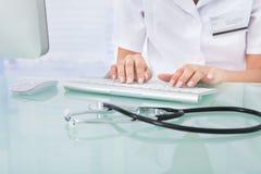Doktorsmaskinskrivning på datortangentbordet i klinik Royaltyfria Bilder