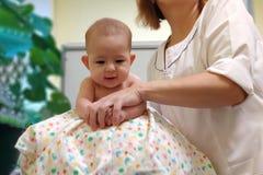 Doktorsmassören gör behandla som ett barn massage på fitball arkivfoton