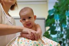 Doktorsmassören gör lyckligt le behandla som ett barn massage på fitball royaltyfria foton