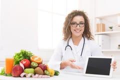Doktorsnäringsfysiolog med grönsaken och frukt som rymmer den tomma digitala minnestavlan royaltyfri fotografi