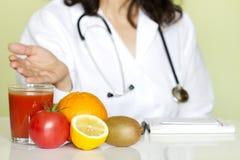 Doktorsnäringsfysiolog i regeringsställning med sunda frukter Arkivbild