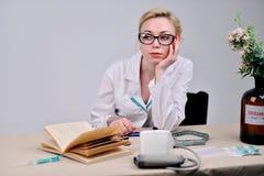 Doktorssammanträdet bak skrivbordet royaltyfri foto
