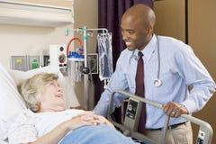 doktorssjukhuspensionär som talar till kvinnan Royaltyfri Bild