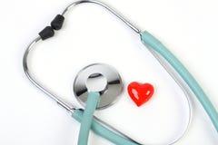 Doktorstethoskop und ein kleines rotes Herz auf weißem Hintergrund Lizenzfreie Stockbilder