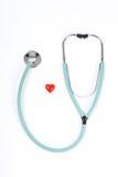 Doktorstethoskop und ein kleines rotes Herz auf weißem Hintergrund Stockfoto