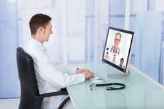 Doktorsvideoconferencing med kollegor till och med datoren Royaltyfria Bilder