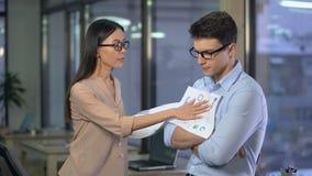 Dokuczający bizneswomanu krytykowania męski pracownik dla błędów w raporcie, kontrola zbiory