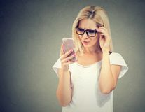 Dokuczająca wzburzona kobieta patrzeje jej telefon komórkowego z frustracją w szkłach Fotografia Stock