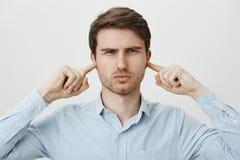 Dokuczający atrakcyjny mężczyzna w koszulowych nakrywkowych ucho z palcami wskazującymi i zezowaniu z poważnym wyrażeniem, być obraz stock