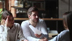 Dokuczający gniewni potomstwo pary klienci trzyma papiery dyskutuje z kierownikiem zbiory wideo