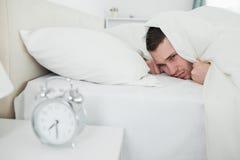 Dokuczający mężczyzna obudzi budzikiem fotografia stock