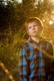 Dokuczający Zmęczony Little Boy w późnego popołudnia słońcu z racą i Co obraz royalty free