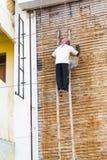 Dokumentär redaktörs- bild En oidentifierad man arbetar på höjder Mycket otrygga scaffoldings Fotografering för Bildbyråer