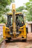 Dokumentär redaktörs- bild gul bulldozer, traktor med en hink som är klar att arbeta, med att hålla ögonen på för folk Arkivfoton