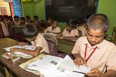 Dokumentär redaktörs- bild Oidentifierade skolbarn studerar i klassrum på den regerings- kommunala skolan royaltyfria foton