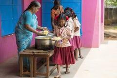 Dokumentär redaktörs- bild Oidentifierat womaen servebarn för lunch på den utomhus- kantin royaltyfria bilder