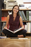 Dokument för läsning för affärskvinnaSitting On Office golv royaltyfri bild