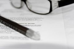 Dokument med den ögonexponeringsglas och pennan Arkivfoto
