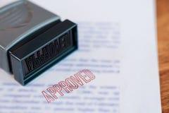 Dokument, som har stämplats utskrivavet på Approved i stor diagonal röd text- och gummistämpel, affärskrediteringsbegrepp arkivfoto