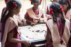 Dokumentalny Redakcyjny wizerunek Dzieci bawić się carrom przy stołem pojęcie dzieciństwo, gry planszowa i móżdżkowy rozwój, i Zdjęcie Royalty Free