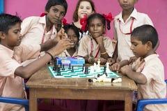 Dokumentalny Redakcyjny wizerunek Dzieci bawić się szachy przy stołem pojęcie dzieciństwo, gry planszowa i móżdżkowy rozwój, i Zdjęcie Royalty Free