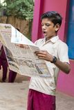 Dokumentalny Redakcyjny wizerunek Młody człowiek z mundurem czyta gazetę w szkole Obrazy Royalty Free