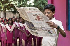 Dokumentalny Redakcyjny wizerunek Młody człowiek z mundurem czyta gazetę w szkole Zdjęcie Stock