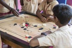Dokumentarisches redaktionelles Bild Kinder, die carrom am Tisch spielen das Konzept der Kindheit und der Brettspiele, der Gehirn Lizenzfreie Stockfotos