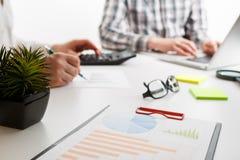 Dokumente mit Diagramm und Diagramm und Stift auf Hintergrund des Arbeitens mit zwei Angestellten lizenzfreies stockbild